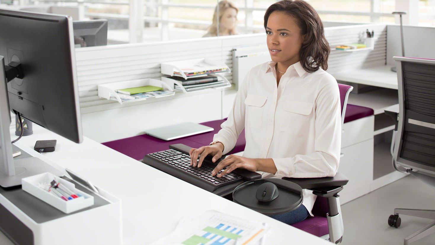 A woman typing at a workstation with a keyboard tray with a mouse and keyboard.