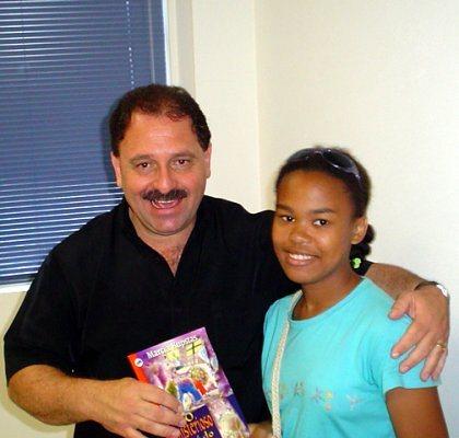 Secretário presenteando uma aluna com livro
